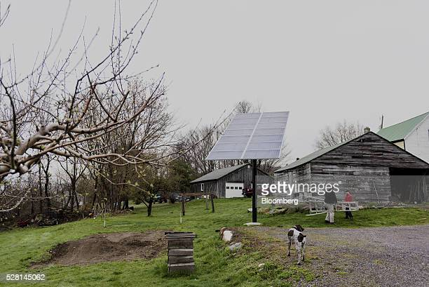 A customer holds a ladder before inspecting a solar panel that is linked to a Tesla Motors Inc Powerwall at a home in Monkton Vermont US on Monday...