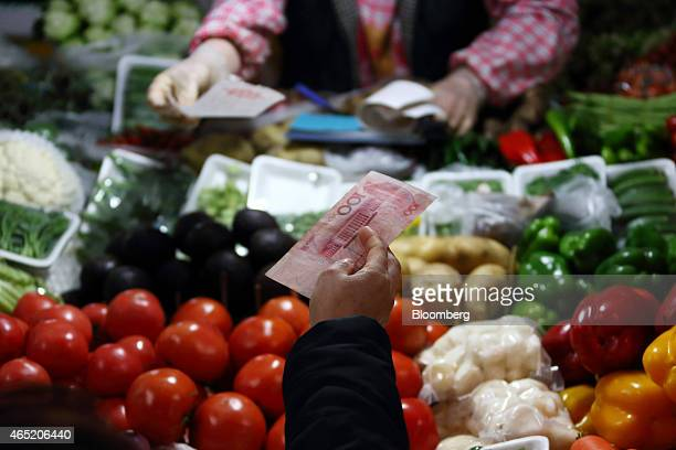 A customer holds a one hundred yuan banknote as she buys vegetables at a market stall in Beijing China on Wednesday March 4 2015 China's leaders are...