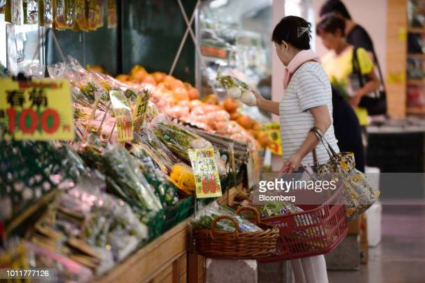 A customer holds a pack of turnip at an Akidai YK supermarket in Tokyo Japan on Friday Aug 3 2018 Rising prices generally make consumers defensive...
