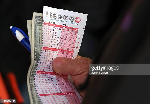 A customer holds a Powerball ticket and money as he waits in line on May 17 2013 in San Francisco California People are lining up to purchase $2...