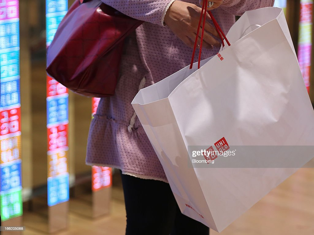 A customer holds a shopping bag at Fast Retailing Co.'s Uniqlo store in the Ginza district of Tokyo, Japan, on Wednesday, April 10, 2013. Fast Retailing, Asia's largest apparel retailer, is scheduled to announce earnings tomorrow. Photographer: Yuriko Nakao/Bloomberg via Getty Images