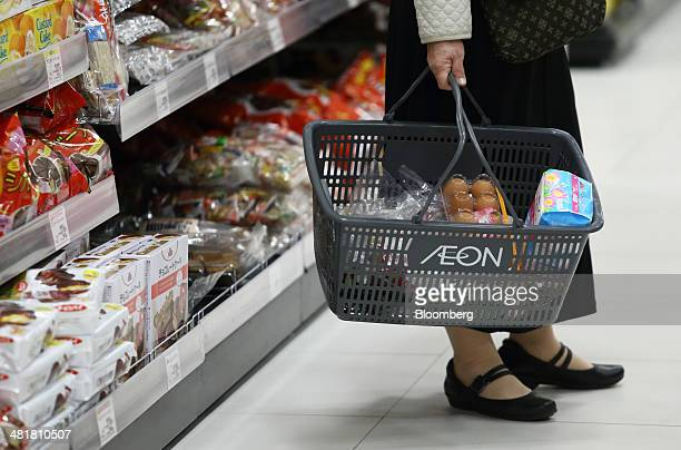 A customer holds a shopping basket at an Aeon Co supermarket in Chiba Japan on Tuesday April 1 2014 Japan's economy will probably withstand a sales...