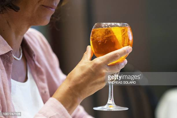 A customer holds a Spritz cocktail in a cafe in central Rome on July 17 2018 Aperol is a historical brand which has existed since 1919 and had a...