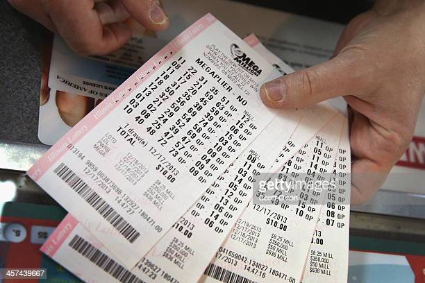 A customer holds a stack of Mega Millions lottery tickets which he purchased for his office pool at a convenience store on December 17 2013 in...