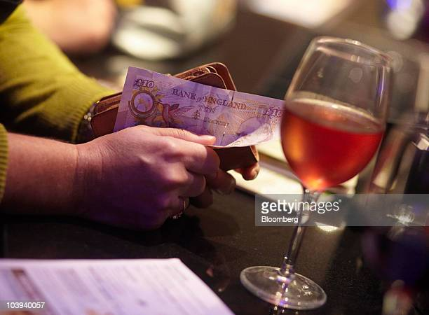Customer holds a U.K. Twenty pound note as she waits to pay for drinks at the Montagu Pyke pub, operated by JD Wetherspoon Plc, in London, U.K., on...