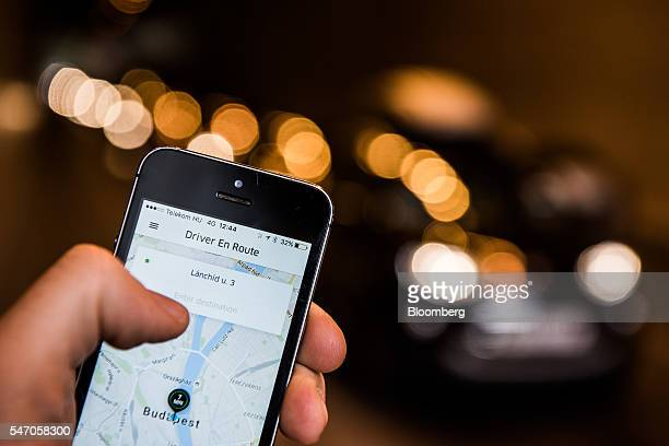 A customer holds an Apple Inc iPhone displaying the Uber Technologies Inc car service taxi application as they await the arrival of a booked vehicle...