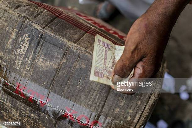 A customer holds an Indian fifty rupee banknote as he stands at a spice store in Thiruvananthapuram Kerela India on Sunday May 31 2015 While...