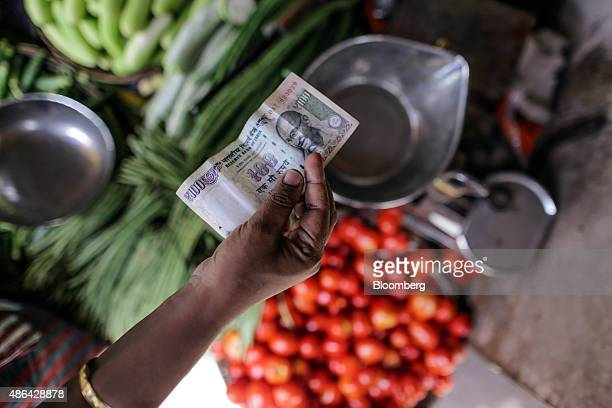 A customer holds an Indian onehundred rupee banknote for a photograph at a in a vegetable market in Mumbai India on Tuesday Sept 1 2015 Prices of the...