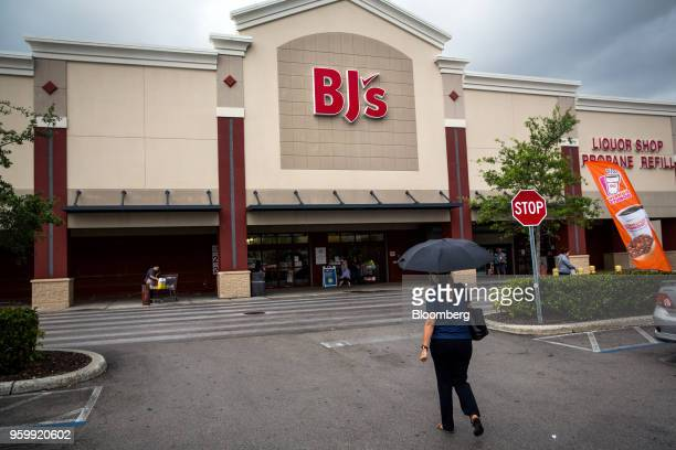 A customer holds an umbrella while walking towards the entrance of a BJ's Wholesale Club Holdings Inc location in Miami Florida US on Thursday May 17...