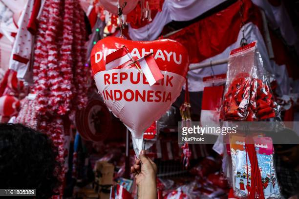 A customer holds balloons in the colors of the Indonesian flag ahead of Indonesian's Independence Day along a market in Jakarta Indonesia on August...