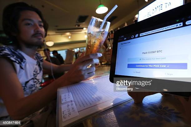 A customer holds his drink purchased with bitcoin for a photograph at The Pink Cow restaurant and bar in Tokyo Japan on Wednesday June 18 2014...