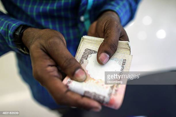 A customer holds Indian 1000 rupee banknotes for a photograph inside an Axis Bank Ltd branch in Mumbai India on Thursday Jan 16 2014 Axis Bank said...