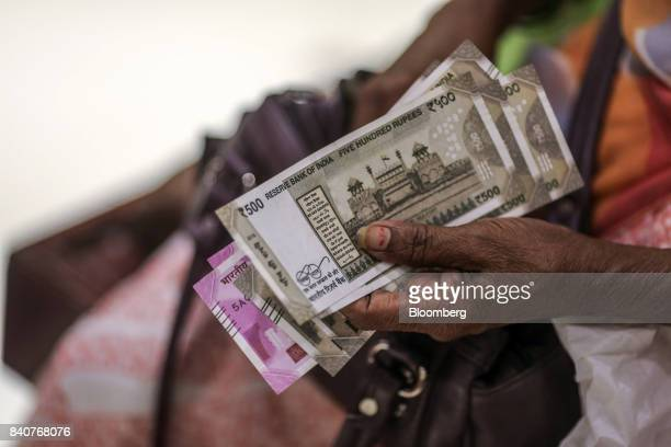 A customer holds Indian rupee banknotes at the PN Gadgil Jewellers Pvt flagship jewelry store in Pune India on Monday Aug 17 2017 About three...