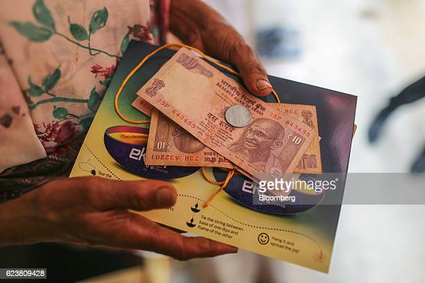 A customer holds Indian rupee banknotes with a greeting from Flipkart Online Services Pvt's Ekart Logistics service in Bengaluru India on Wednesday...