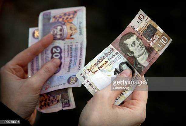 Customer holds Scottish twenty pound notes, left, and a Scottish ten pound note, issued by Clydesdale Bank, in this arranged photograph in Edinburgh,...