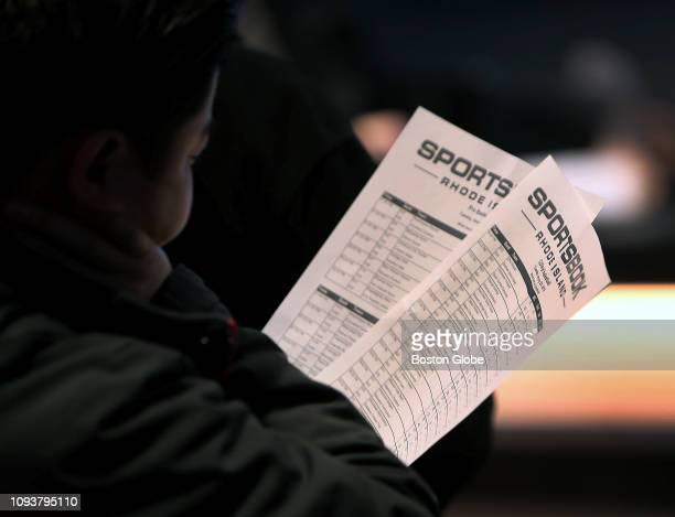 A customer holds sheets with betting information at the sports book bar at Twin River Casino in Lincoln RI on Jan 29 2019
