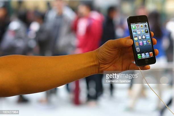 A customer holds the iPhone 5 at the Apple flagship store on George street on September 21 2012 in Sydney Australia Australian Apple stores are the...