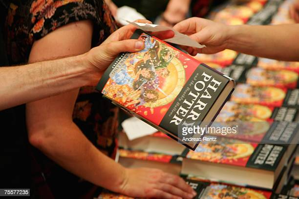 A customer holds the last book by JK Rowling Harry Potter and the Deathly Hallows in his hands at a bookstore after its release at 101am on July 21...