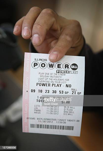 A customer holds up a Powerball lottery ticket at a 7Eleven store on November 28 2012 in Chicago Illinois Jim Bayci who owns the store estimates more...