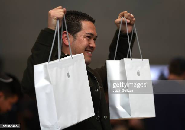 A customer holds up two bags after purchasing the new iPhone X at an Apple Store on November 3 2017 in Palo Alto California The highly anticipated...