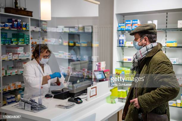 A customer in a pharmacy in downtown Jena wearing a protective face mask on April 3 2020 in Jena Germany A threepart city ordinance is going into...