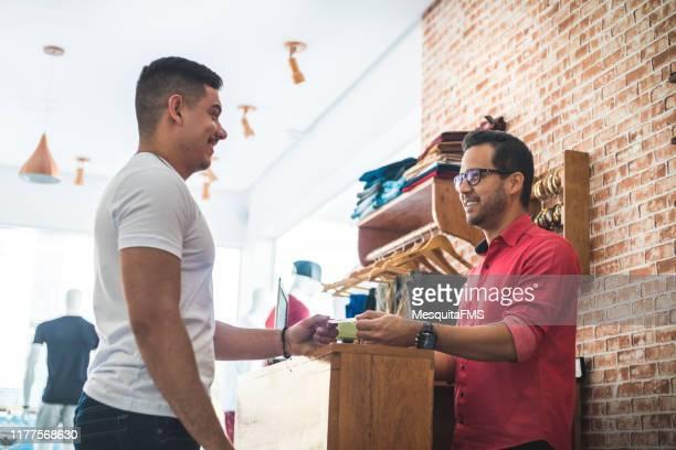 cliente na loja de roupas está pagando através do cartão de crédito - attending - fotografias e filmes do acervo
