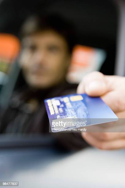 Customer in drive-thru holding out credit card