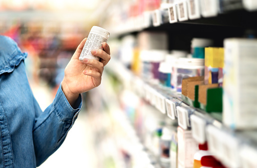 Customer in pharmacy holding medicine bottle. Woman reading the label text about medical information or side effects in drug store. Patient shopping pills for migraine or flu. 1140560047