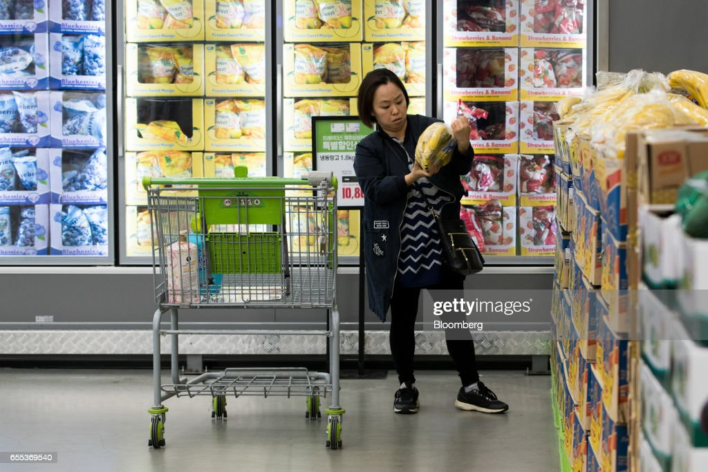 A customer inspects a bag of bananas at an E-Mart Inc. Traders store in the Starfield Hanam shopping complex, operated by Shinsegae Co., in Hanam, Gyeonggi, South Korea, on Wednesday, March 15, 2017. Photographer: SeongJoon Cho/Bloomberg via Getty Images