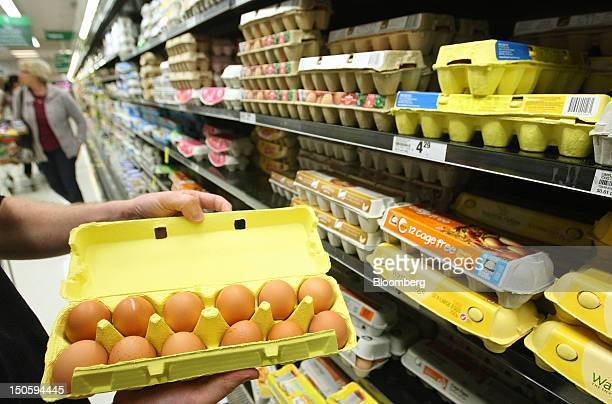 A customer inspects a carton of eggs at a Woolworths Ltd supermarket in Perth Australia on Wednesday Aug 22 2012 Woolworths Australia's largest...