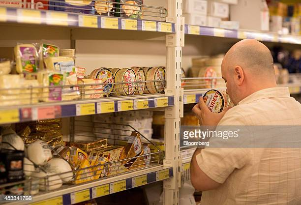 A customer inspects a French 'President' branded camembert cheese produced by Groupe Lactalis SA inside a supermarket in Moscow Russia on Friday Aug...