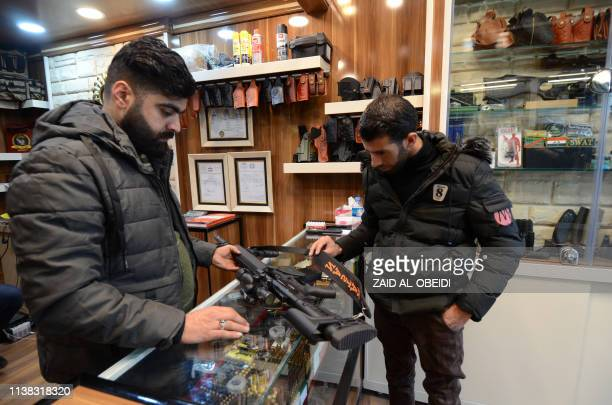 A customer inspects a rifle sold in a gun shop in the northern Iraqi city of Mosul on January 28 2019 Hunting rifles pistols and towers of ammunition...