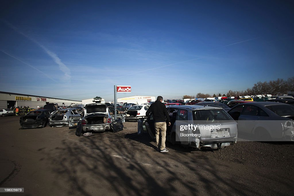 A customer inspects a scrapped Audi AG automobile in the yard of the Desguaces La Torre scrapyard in Madrid, Spain, on Thursday, Dec. 13, 2012. Spain has completed the debt sales it planned for this year and started raising funds for 2013, buying time for Prime Minister Mariano Rajoy as he decides whether to seek a European bailout. Photographer: Angel Navarrete/Bloomberg via Getty Images