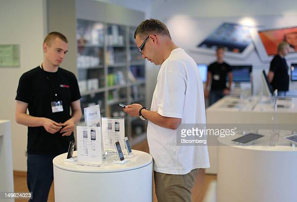 A customer inspects an Apple Inc iPhone 4S inside a reStore a premium Apple product reseller in Moscow Russia on Wednesday Aug 1 2012 OAO Mobile...