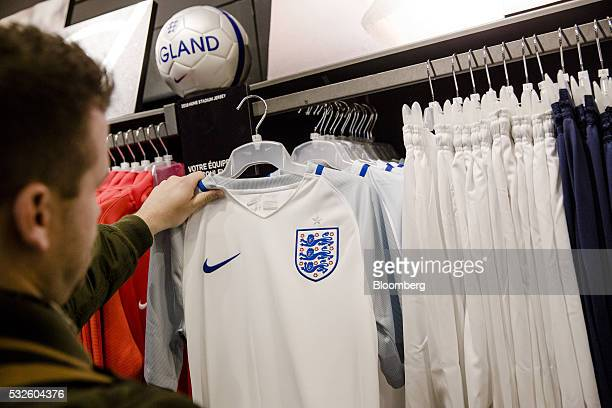 A customer inspects an official England national football team jersey inside the Nike Inc sports apparel store in Paris France on Thursday May 19...