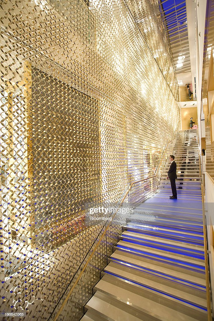 A customer inspects the interior of the Louis Vuitton 'maison,' the London flagship store for LVMH Moet Hennessy Louis Vuitton SA, in New Bond Street in London, U.K., on Tuesday, May 25, 2010. The new London LV maison has been designed by the New York-based architect, Peter Marino, who also worked on the brand's Champs Elysees maison. Photographer: Chris Ratcliffe/Bloomberg via Getty Images