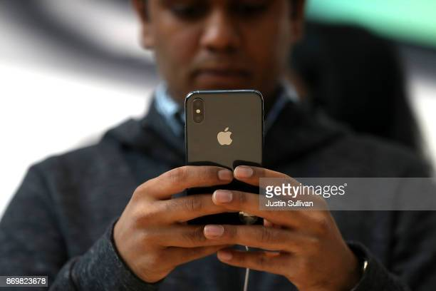A customer inspects the new iPhone X at an Apple Store on November 3 2017 in Palo Alto California The highly anticipated iPhone X went on sale around...