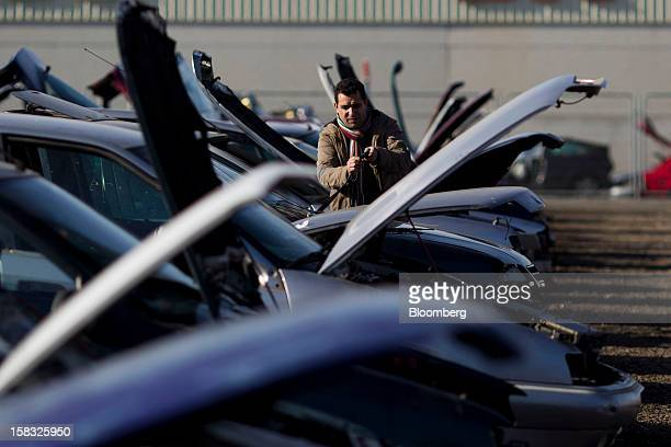 A customer inspects windscreen wiper blades while checking for spare parts on a scrapped automobile in the yard of the Desguaces La Torre scrapyard...