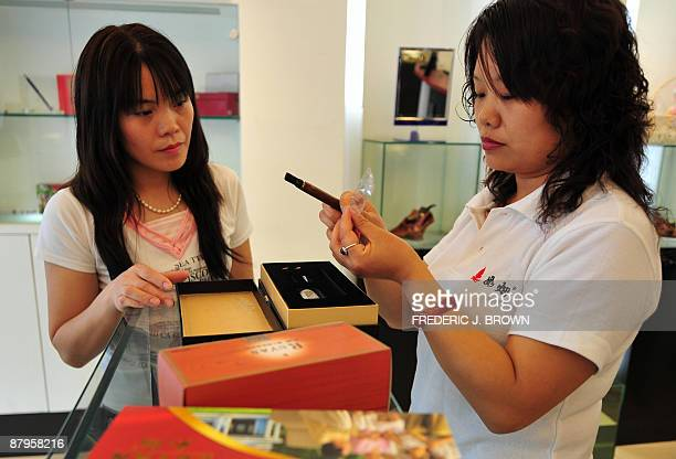 A customer is assisted by a salesperson at a shop selling electric smoking products in Beiijng on May 25 2009 designed by Hon Lik the inventor of the...