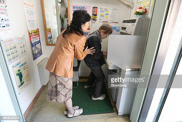 A customer is assisted by Yuriko Asahara former manager of Japan Post Co's Hachioji Nagabusa branch left at an automated teller machine inside the...