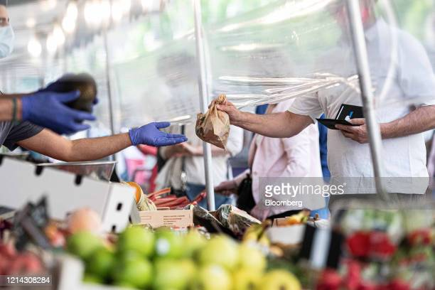 A customer is handed their purchase while standing beside a protective cellophane screen on a fruit and vegetable stall at Marche SaxeBreteuil in...