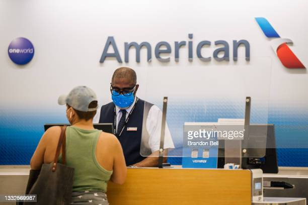 Customer is helped at an American Airlines check-in counter at the George Bush Intercontinental Airport on August 05, 2021 in Houston, Texas....