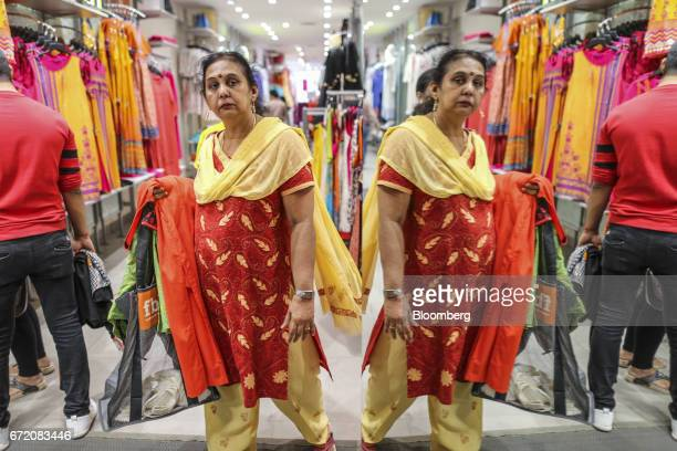 A customer is reflected in a mirror as she browses clothes at a Big Bazaar hypermarket operated by Future Retail Ltd in Mumbai India on Sunday April...