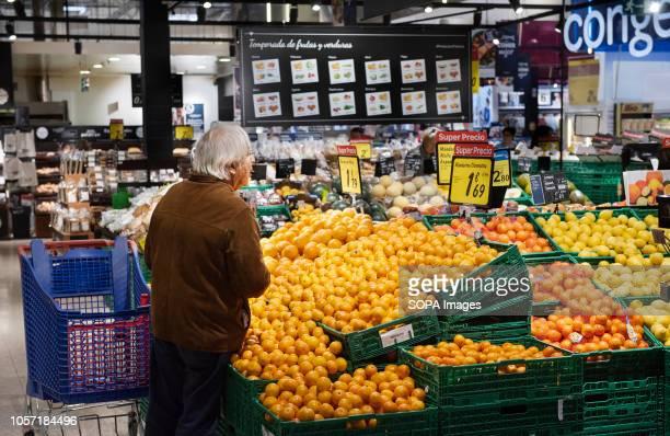 A customer is seen purchasing mandarin orange at Carrefour supermarket in Spain