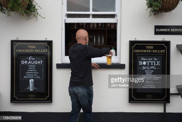 Customer is served a pint of beer via a window at the Crooked Billet pub on July 04, 2020 in Leigh-on-Sea, United Kingdom. The UK Government...