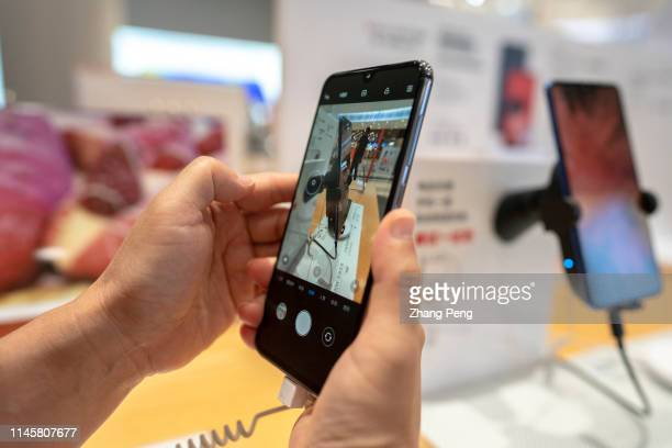 Customer is trying the latest Xiaomi 9 mobile phone in a MI Shop. On May 20, MI Group released its financial report of the first quarter of 2019,...
