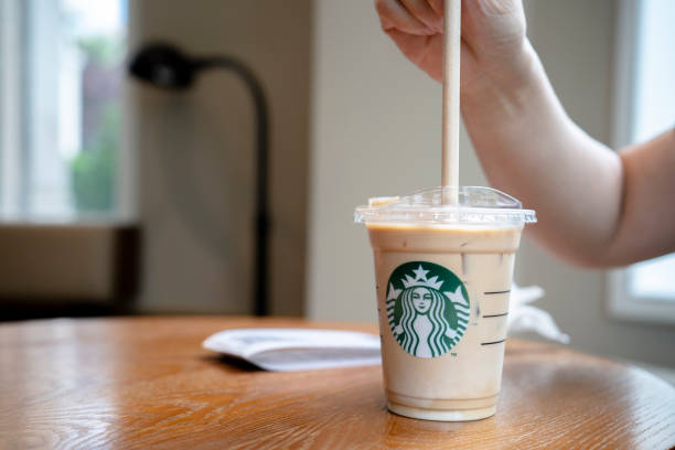 customer is using a paper straw to drink a cold starbucks latte to picture