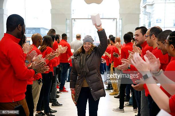 A customer is welcomed by Apple employees inside the new Apple store SaintGermain during the first opening day on December 03 2016 in Paris France...