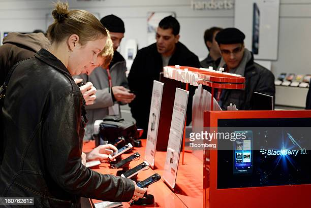 Customer Katie Strong views a Blackberry Z10 device on the first day of sales at a Rogers Communications Inc store in Toronto Ontario Canada on...