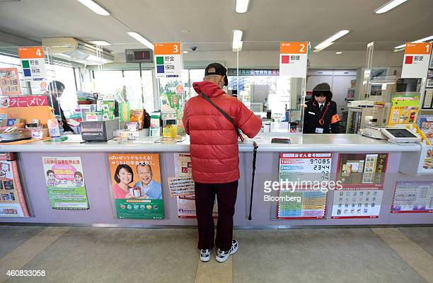 Customer Katsumi Amano withdraws money from his bank account at a Japan Post Co branch in Hachioji Japan on Tuesday April 15 2014 Companies are...